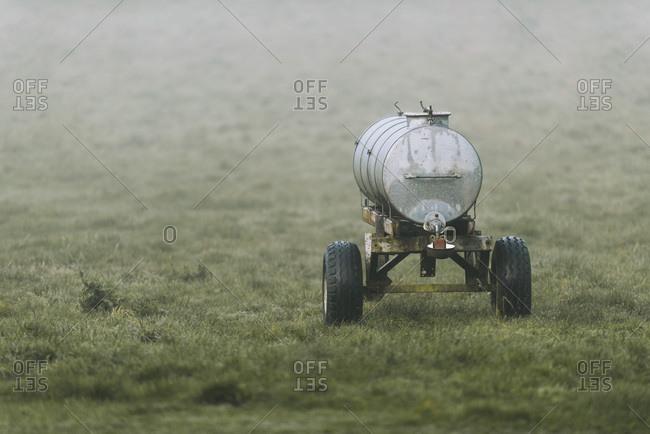 Vintage liquid manure spreader in misty meadow in autumn.