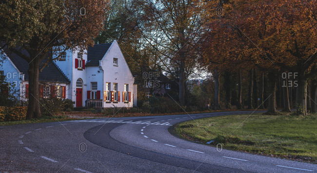 White colored house along road with orange colored autumn trees.