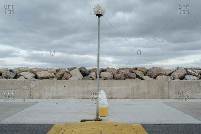 Road signs and concrete construction in a pier on a cloudy day