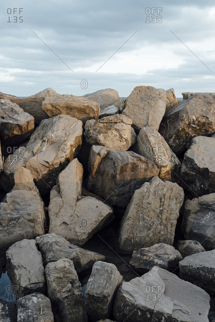 Rocks piled up in a pier on a cloudy day