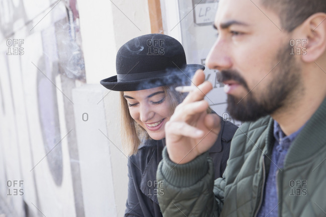 Young man smoking beside his smiling girlfriend