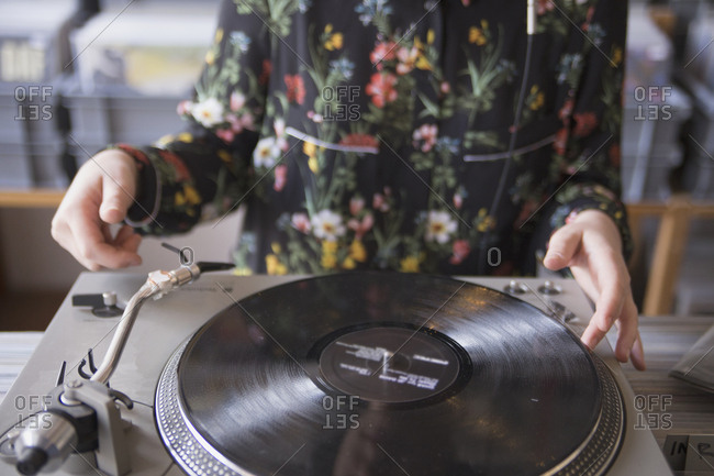 Hands of young woman using record player