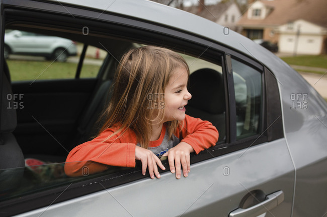 Smiling girl looking out open car window