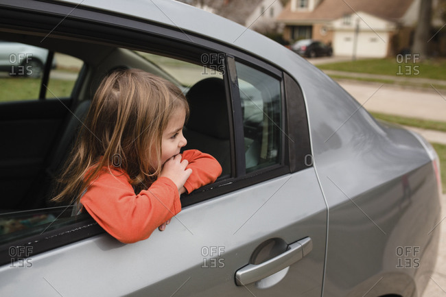 Girl looking out open window of car