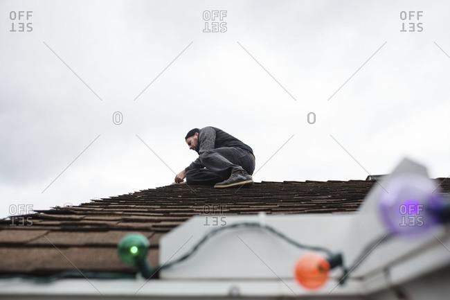 Man on roof hanging Christmas lights