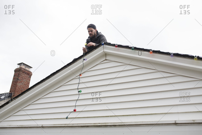 Man hanging Christmas lights from rooftop