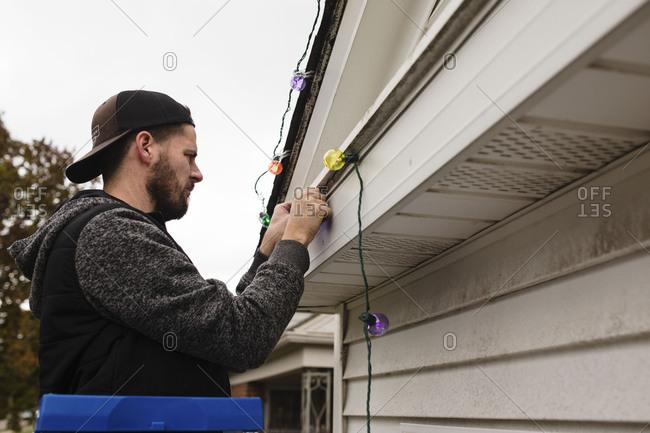 Man hanging Christmas lights on eaves of house