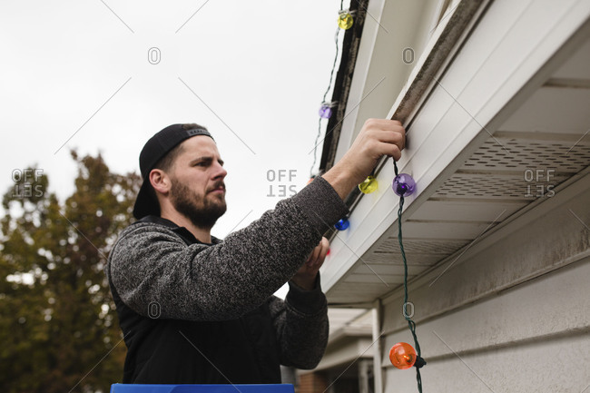 Man attaching Christmas lights to eaves of house