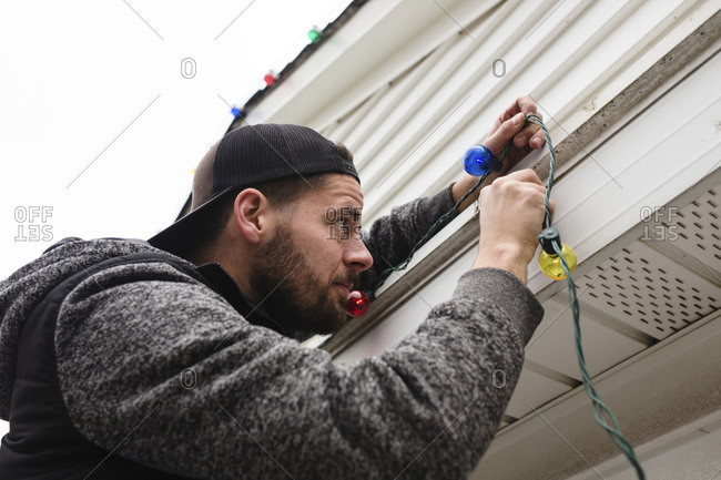Man attaching Christmas lights to house