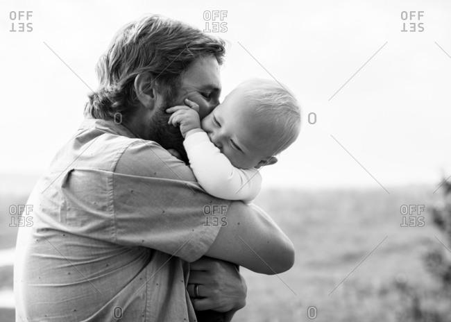 Father tightly hugging baby