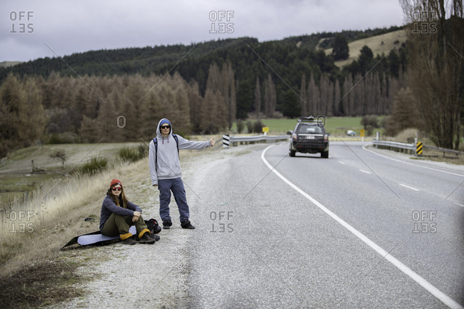 Snowboarders hitchhiking along highway