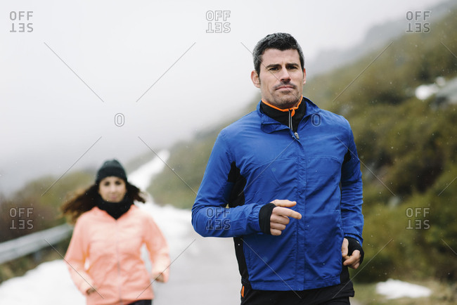 Man and woman athletes running on a mountain road under the snow in winter