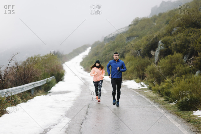 Couple of athletes running in winter on a mountain road under the snow