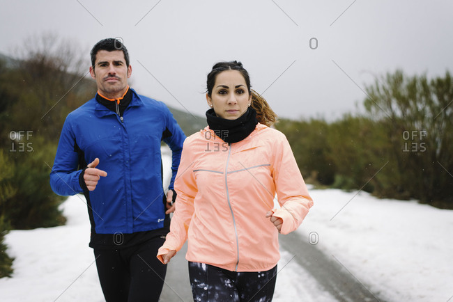 Front view of athletes running on mountain road under the snow in winter