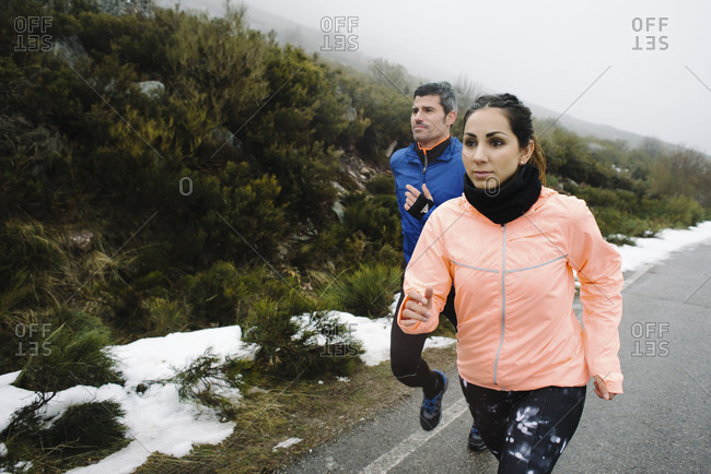 Couple of athletes running on a mountain road under the snow in winter