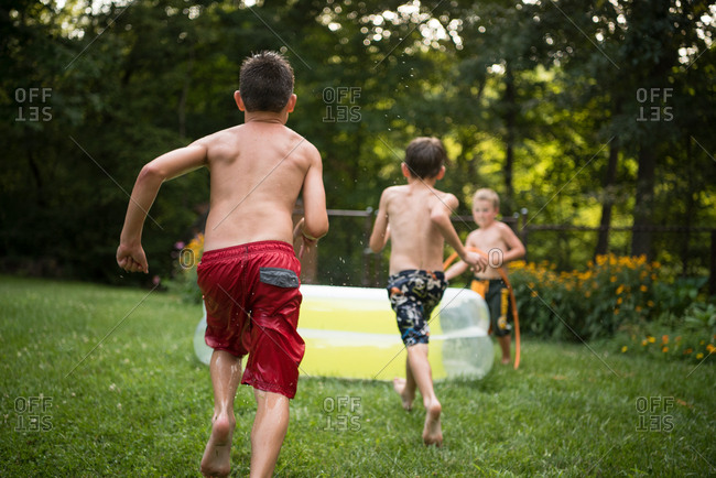 Three boys running toward a pool