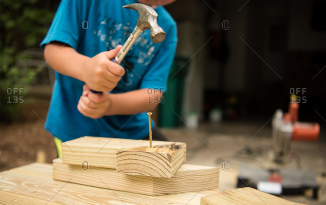 Young boy with hammer and nail building