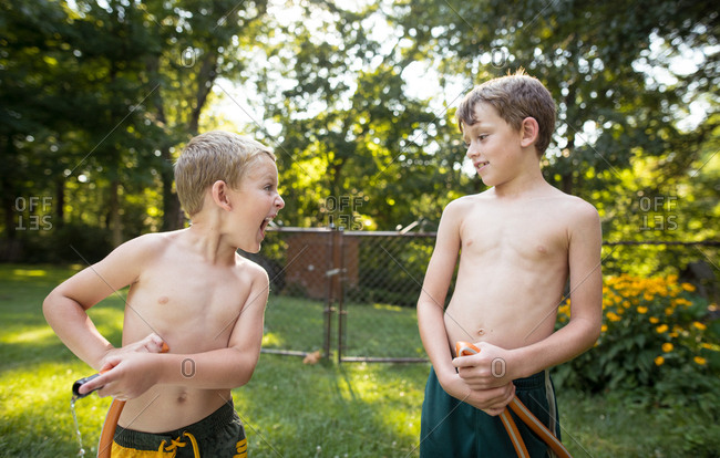 Two young boys fighting over a hose