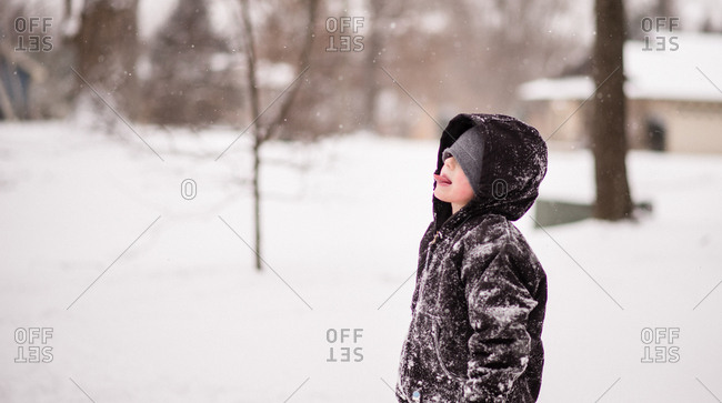 Boy in winter coat covered with snow catching snowflakes on his tongue