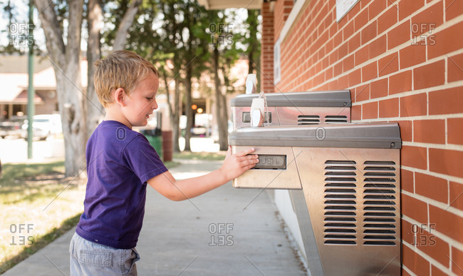 Boy turning on a drinking fountain