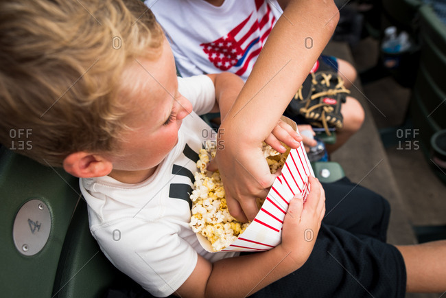 Young boy eating popcorn and not wanting to share
