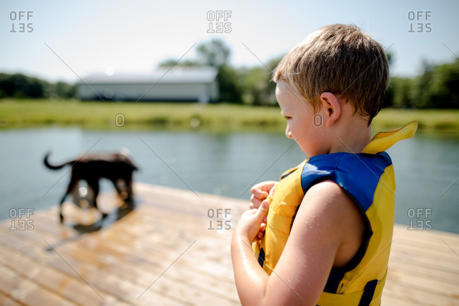 Young boy and dog on dock by pond