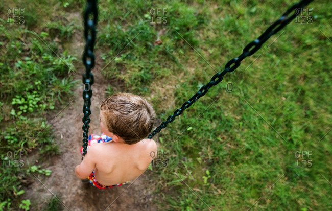 Top view of a boy sitting still on a swing