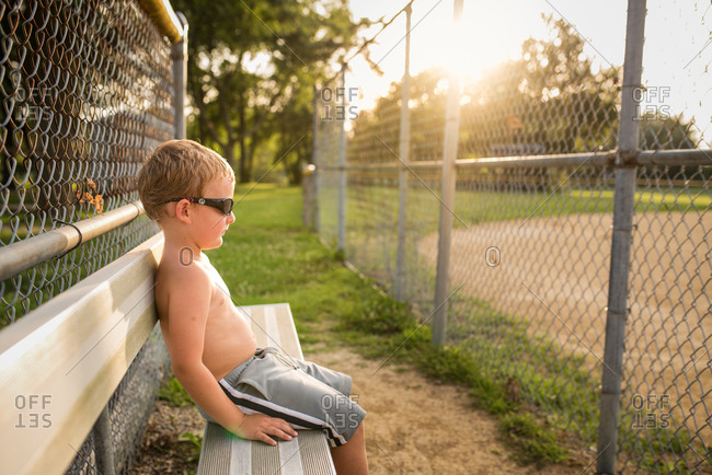 Shirtless boy sitting on bleacher
