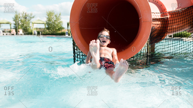 Young boy splashing out of a water slide