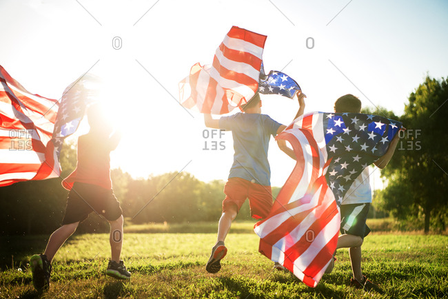 Three boys running on grass with American flags