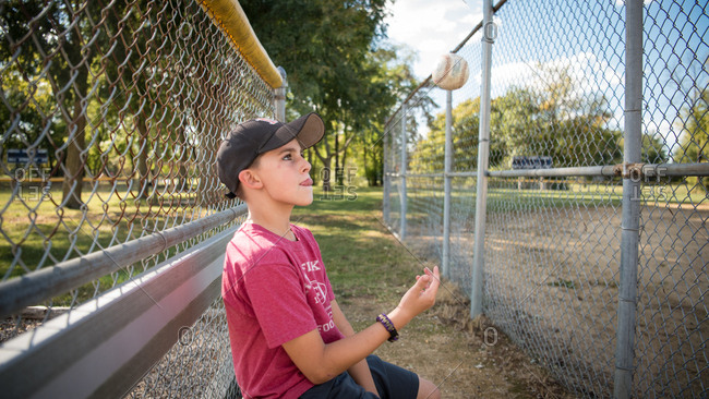 Boy sitting on bench tossing baseball into the air
