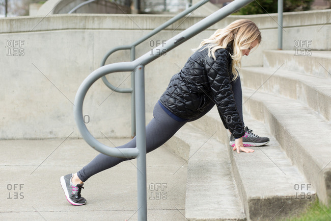 Blonde woman stretching her legs on steps