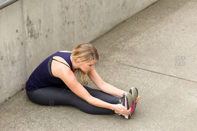 Woman sitting on ground stretching her legs before a workout