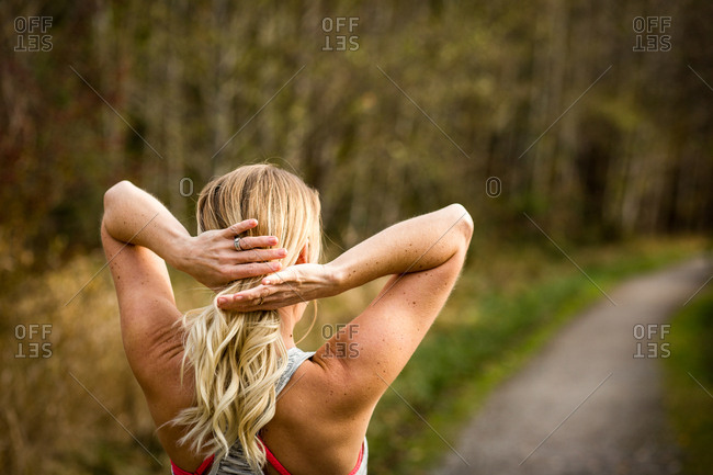 Blonde woman fixing hair during workout