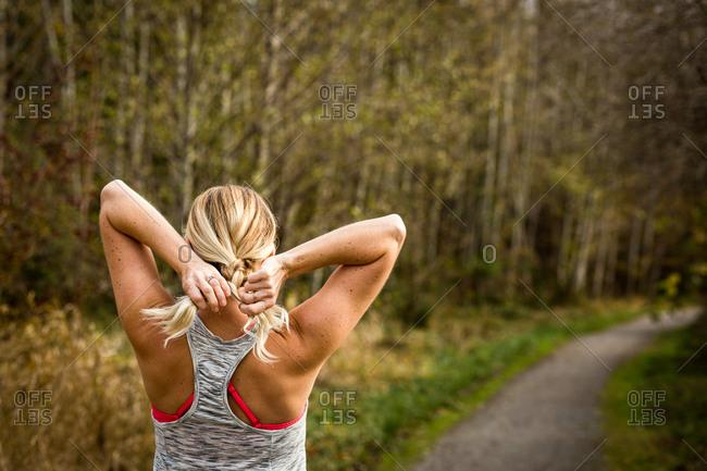 Blonde woman braiding hair during workout