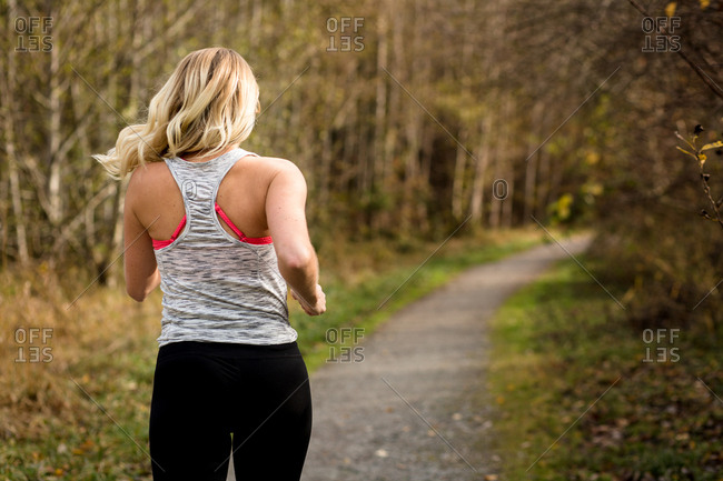 Rear view of woman running on trail in a forest