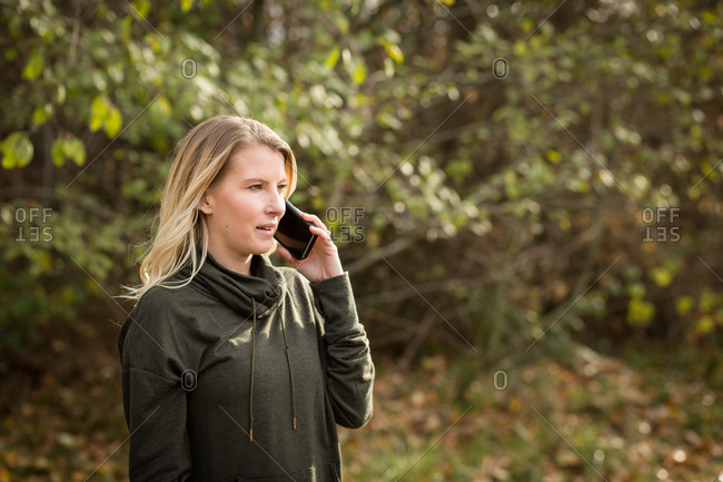 Woman talking on cell phone during an autumn workout