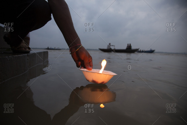 Person placing lit candle in Ganges river