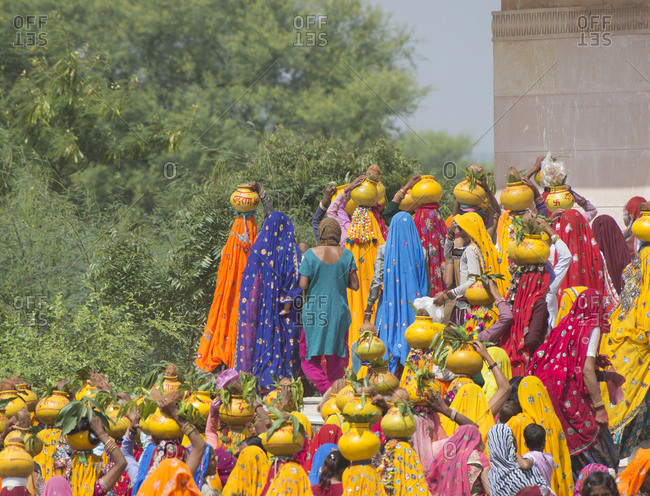 Rajasthan, India - October 8, 2013: Many people carrying pots on their heads during religious celebration of Krisna