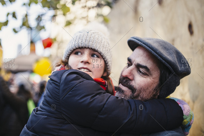 Girl with her arms around father's neck