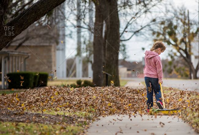 Rear view of a boy raking leaves on a sidewalk with a broom
