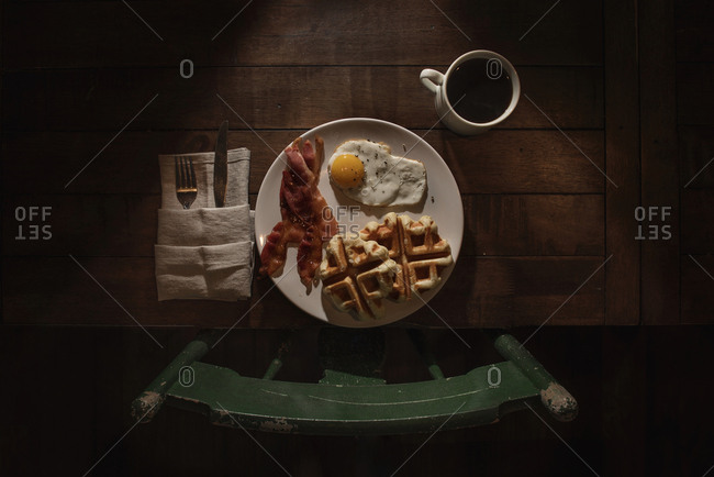 Waffles, eggs and bacon served with coffee