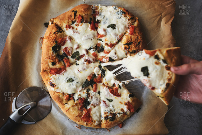 Hand grabbing slice of homemade pizza