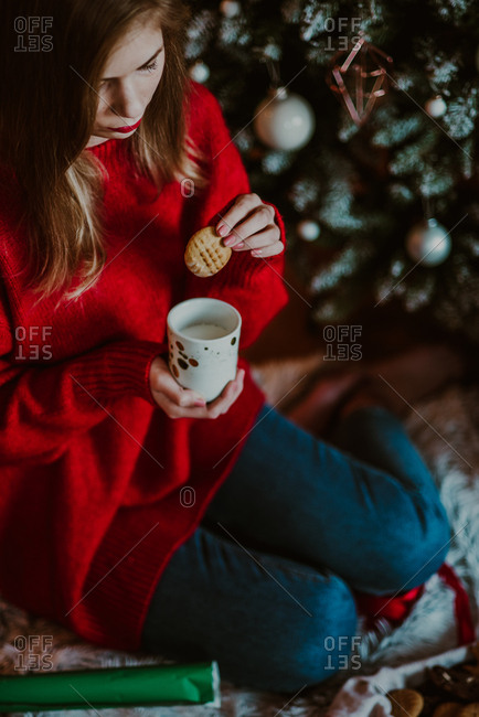 Woman dipping cookie into milk by Christmas tree