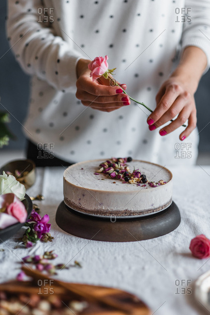 Woman decorating a cake with fresh flowers