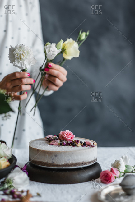 Woman decorating a cake with flowers