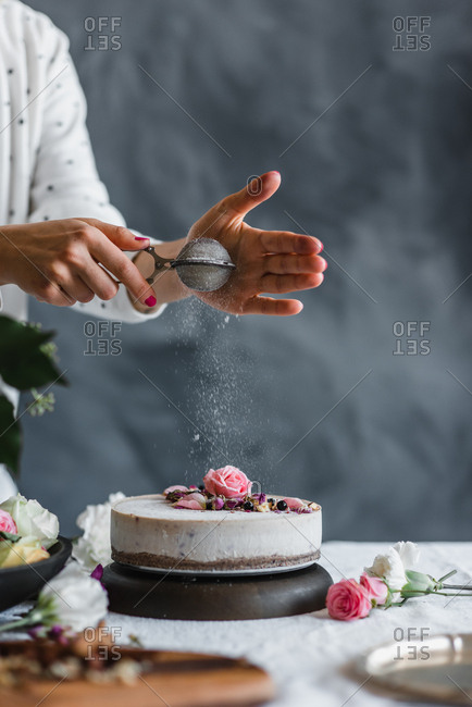 Woman sprinkling powdered sugar on a cake with flowers