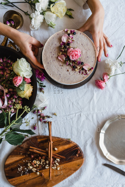 ... Overhead view of a woman decorating a cake with flowers & cake decorating stock photos - OFFSET