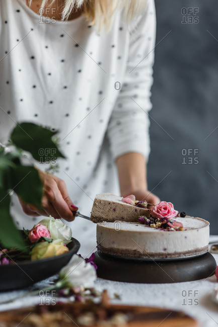 Woman serving a slice of cake with flowers