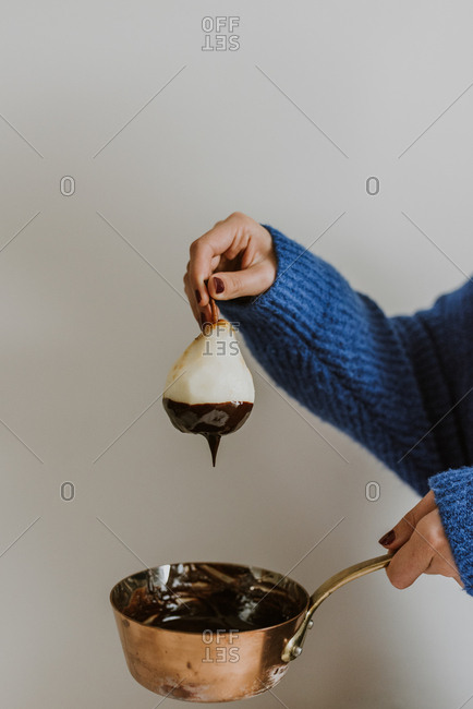 Woman dipping pear into melted chocolate sauce